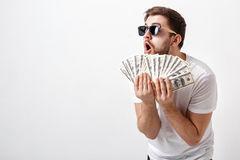 Handsome smiling man with beard in shirt holding a lot of hundre. Young handsome smiling man with a beard in a white shirt holding a lot of hundred-dollar bills royalty free stock images