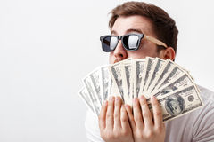 Handsome smiling man with beard in shirt holding a lot of hundre. Young handsome smiling man with a beard in a white shirt holding a lot of hundred-dollar bills stock photo