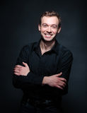 Handsome smiling man in black. Against the black background Stock Photos