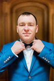 Handsome smiling man in blue suit fixin his bow tie in rich wooden interior Stock Image