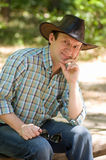 Handsome smiling man with with cowboy hat. In the forest Royalty Free Stock Photo