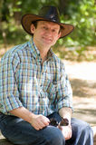 Handsome smiling man with cowboy hat. In the forest Royalty Free Stock Photos