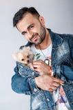 Man in denim jacket holds pomeranian dog. royalty free stock photo