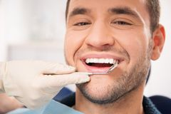 Handsome smiling man at dentist. Handsome smiling man at doing checkup at dentist's surgery Stock Image