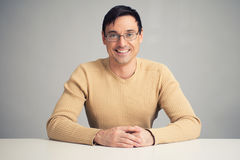 Handsome smiling man on a desk Stock Photo