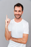 Handsome smiling man having an idea and pointing finger up Stock Images