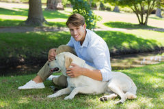 Handsome smiling man with his labrador in the park Royalty Free Stock Photos