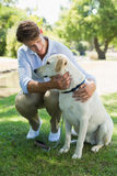 Handsome smiling man with his labrador in the park Stock Image