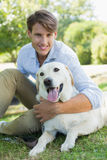 Handsome smiling man with his labrador sitting in the park Stock Photography