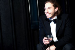 Handsome smiling man holding a glass of wine Royalty Free Stock Image