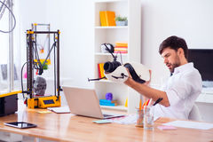 Handsome smiling man holding model printed on 3d printer. Fire away. Pleasant cheerful handsome man holding model printed on 3d printer and sitting at the table royalty free stock photo