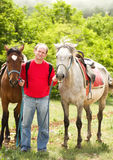 Handsome smiling man with horses Stock Photos