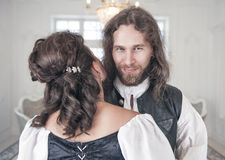 Handsome smiling man in medieval clothes with beautiful woman. Handsome smiling men in medieval clothes with beautiful women in the room Stock Image