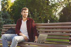 A smiling man with laptop outdoors. Handsome smiling man in a pleasant atmosphere outdoors, in the park working with laptop. Technology, communication, education Royalty Free Stock Images