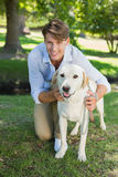 Handsome smiling man posing with his labrador in the park Royalty Free Stock Photos