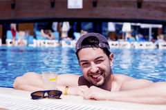 Handsome smiling man relaxing in the swimming pool with cold  drink. Young smiling  man enjoying his summer vacation  swimming pool Royalty Free Stock Photo