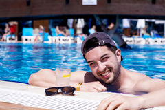 Handsome smiling man relaxing in the swimming pool with cold  drink. Young smiling  man enjoying his summer vacation  swimming pool Royalty Free Stock Images