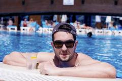 Handsome smiling man relaxing in the swimming pool with cold  drink. Young smiling  man enjoying his summer vacation  swimming pool Royalty Free Stock Photography