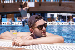Handsome smiling man relaxing in the swimming pool with cold  drink. Young smiling  man enjoying his summer vacation  swimming pool Stock Images