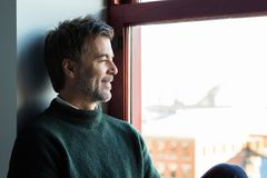 Handsome smiling man relaxing by the window. He is confident and looking by the window stock photography