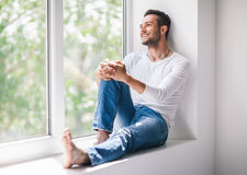 Handsome smiling man relaxing on window sill. Carefree concept stock photo
