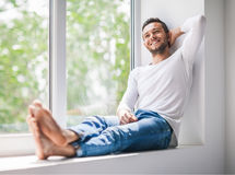 Handsome smiling man relaxing on window sill. Carefree concept royalty free stock photos