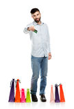 Handsome smiling man with shopping bags and holding credit card Royalty Free Stock Images