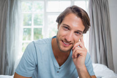 Handsome smiling man sitting on bed looking at camera Stock Images
