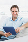 Handsome smiling man sitting on the sofa using his tablet pc Stock Photography