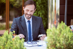 Handsome smiling man sitting at the table Royalty Free Stock Image
