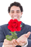 Handsome smiling man in a suit holding a red rose and offers it Stock Image