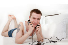 Handsome smiling man with tatoo listening music Royalty Free Stock Photos