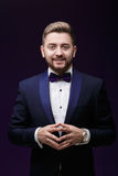 Handsome smiling man in tuxedo and bow tie looking at camera. Fashionable, festive clothing. emcee on dark background Royalty Free Stock Image