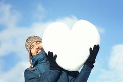 Handsome smiling man in winter clothes holding a big heart made of snow, on the blue sky background. Declarations of love, stock photos
