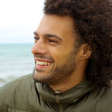 Handsome smiling man in winter in front of ocean closeup Royalty Free Stock Photo