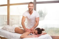 Handsome smiling masseur doing massage. For young beauty brunette women in spa salon in front of large window royalty free stock images