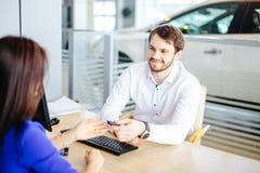 Salesman handing over car key to a customer woman royalty free stock image