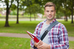 Handsome smiling student carrying folder. On campus at college Royalty Free Stock Images