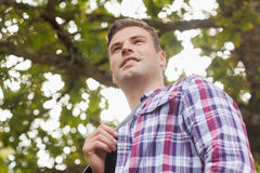 Handsome smiling student looking away. On campus at college Stock Photography