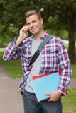 Handsome smiling student standing and phoning. On campus at college Royalty Free Stock Images