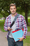 Handsome smiling student standing and texting. On campus at college Stock Image