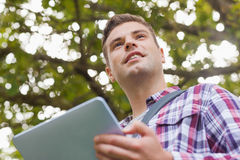 Handsome smiling student using tablet. On campus at college Stock Photo