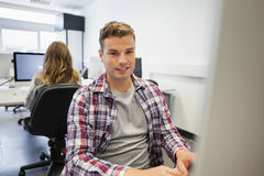 Handsome smiling student working on computer Royalty Free Stock Image