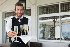 Handsome smiling waiter offering flute of champagne Stock Photo
