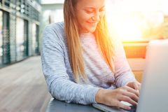 Handsome smiling woman with laptop sitting in street cafe, browsing web and social network feed, joyfully chatting with friends. Outdoors Royalty Free Stock Photography