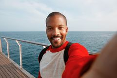 Handsome smiling young African-American hipster man taking selfie with happy face at the beach. Blue sea on the blurred Royalty Free Stock Images