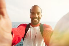 Handsome smiling young African-American hipster man taking two hand selfie with happy face outdoors of city. Blue sea on Royalty Free Stock Photos