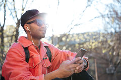 Handsome smiling young african man outdoors using mobile phone. Image of handsome smiling young african man sitting outdoors in park wearing sunglasses and cap Royalty Free Stock Image