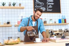 handsome smiling young barista pouring coffee royalty free stock photos