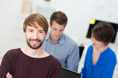 Handsome smiling young businessman. Standing looking at the camera with folded arms as his colleagues work in the office in the background stock photography
